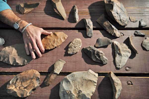 Douglas Bamforth, Anthropology professor for the University of Colorado at Boulder, places his hand on one of the artifacts unearthed in Boulder. The artifacts, which may have been made during the Clovis period nearly 13,000 years ago, were neatly arranged in a cache near where this portrait was taken, suggesting that the users of these instruments may have intended to reuse them. © Glenn J. Asakawa/University of Colorado)