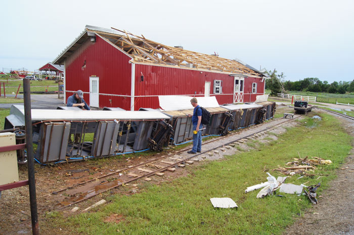 Staff survey one of the Orr Family Farm trains as the damaged Animal Barn remains standing in the background