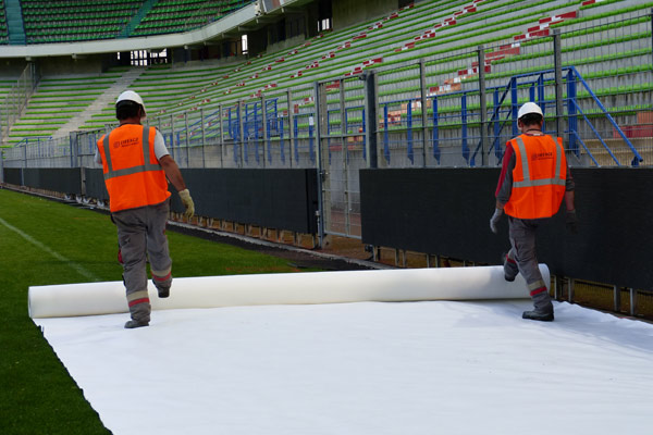 Workers roll out a protective covering over the pitch.