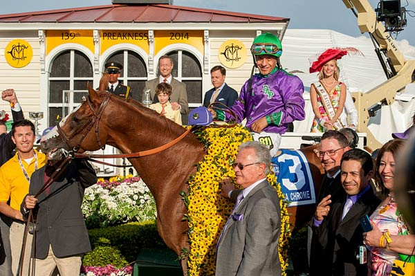 California Chrome in the winners circle of the 139th Preakness Stakes. Jockey Victor Espinoza up, trainer Art Sherman at horse's shoulder, behind him is son and assistant Alan Sherman (wearing glasses) and Espinoza's brother Jose Espinoza.