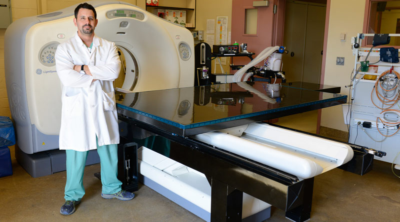 Jason Peters, RVT, RLAT, a technician in the hospital's Diagnostic Imaging Service, with his new CT table.